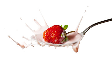fresh strawberry splashing into the spoon full of yoghurt