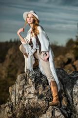 Fashion photo of beautiful woman at mountain rock
