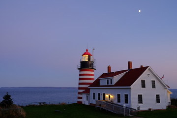 Dusk falls over the W Quoddy Lighthouse on a full moon