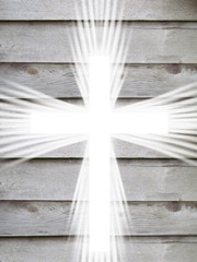 white cross with light rays and old wooden grey background