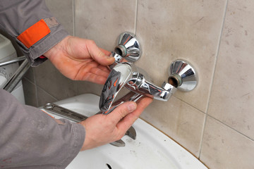 Plumber fixing faucet in a bathroom, replace chromium tap