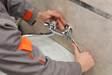 Plumber hands fixing water  tap with spanner, faucet and tool