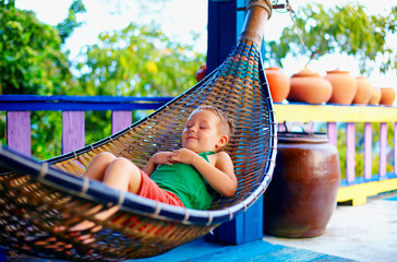 cute boy relaxing in hammock. Enjoying life on tropical island