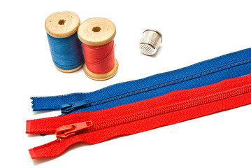 two zipper, thimble and spools of thread