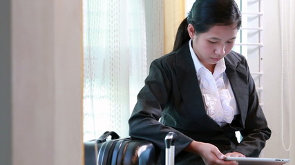 Business woman waiting for travel and using tablet computer