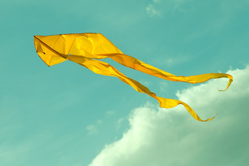 Yellow kite flying in the cloudy sky. Toned photo