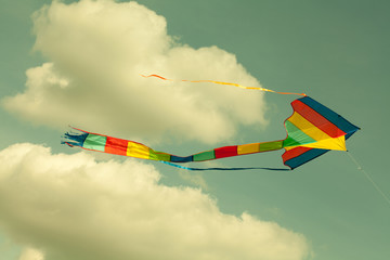 Multicolor kite flying in the cloudy sky. (Toned photo.)