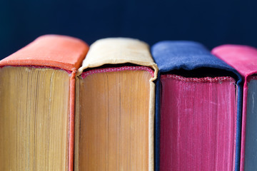 Vintage books with colored spines and pages.