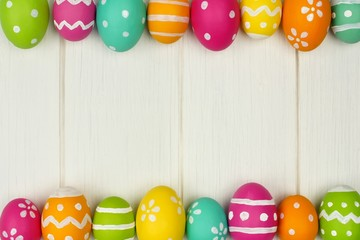 Colorful Easter egg frame against white wood
