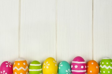 Colorful Easter egg bottom border against white wood