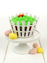 Spring cupcake decorated with grass and white picket fence