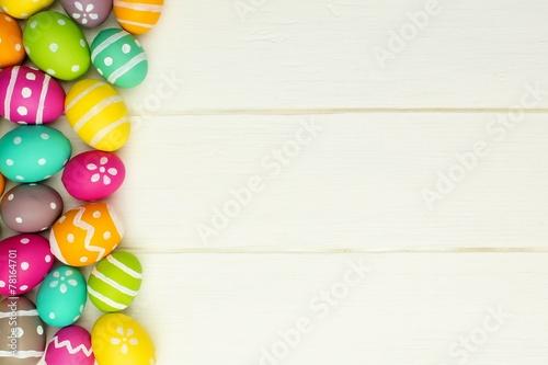 Leinwandbild Motiv Colorful Easter egg side border against white wood