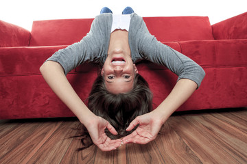 Smiling woman with legs up on couch in living room