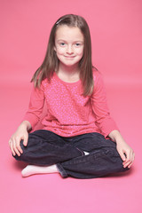 young girl poses for a picture isolated on pink