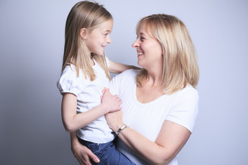 A mother with is daughter over gray background