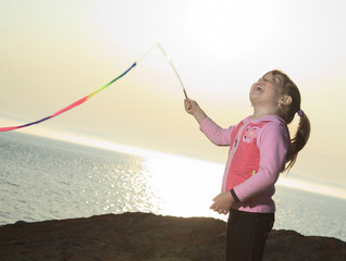 Little girl play with a multi-color stick on sunset