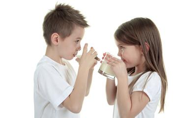 Little boy drinking milk on white background. Studio shot