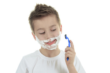 playful little young boy shaving face over white background