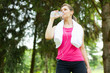 Woman drinking water while running in a park