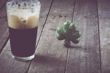 Pint of Stout Beer with Green Shamrock with Vintage Film Filter
