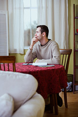 Finances: Man Pauses To Think While Paying Bills