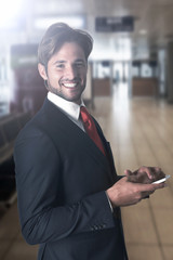 businessman smiling while using his mobile