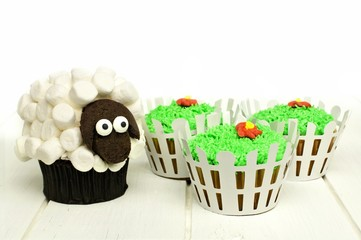 Easter lamb and grass cupcakes on a white wood
