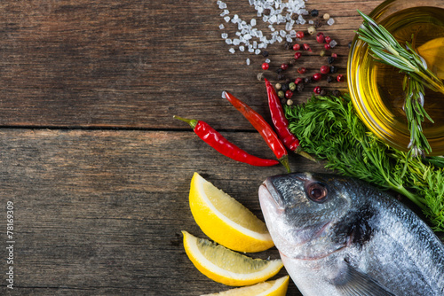 canvas print picture Fresh whole sea fish with aromatic herbs and spices
