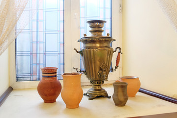 Old samovar and ceramic jugs on the windowsill