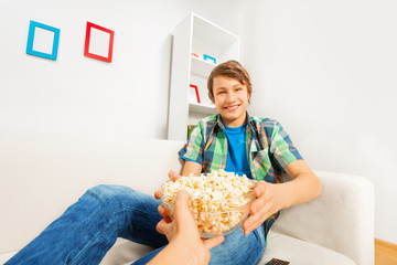 Happy boy holds popcorn bowl from someone's hand