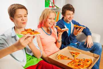 Teenagers holding pizza pieces and eating