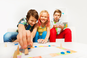 Happy teenagers play table game together at home
