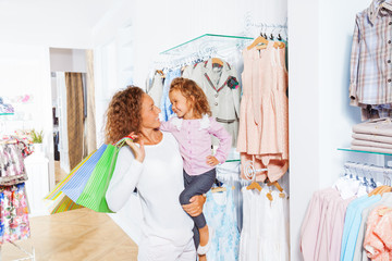 Woman holds shopping bags with her small daughter