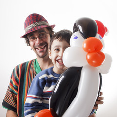 Balloon twister and little boy with penguin.