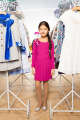 Small Asian girl with standing between clothes