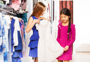 Girls shopping and one of them holding white dress