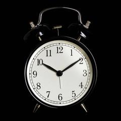 Black alarm clock isolated on black background