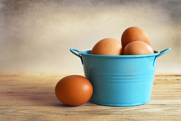 Chicken eggs in a blue metal bowl