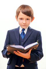 Business child in suit and tie posing with notepad
