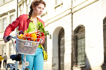 Pretty spring woman with bicycle and groceries in old town stree
