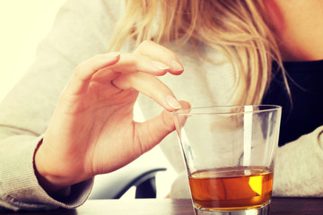 Yound woman in depression, drinking alcohol