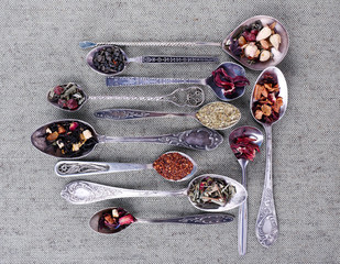 Tea in metal spoons on grey fabric background