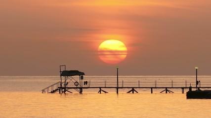 beautiful sunrise over pier in sea - telephoto lens, timelapse 4