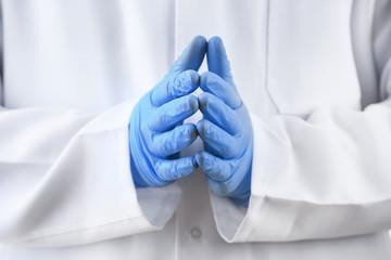 Doctor hands in sterile gloves on background