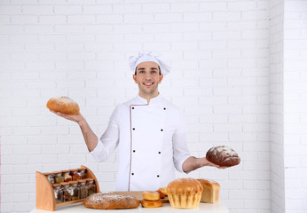 Baker in kitchen at table with freshly loaves of bread