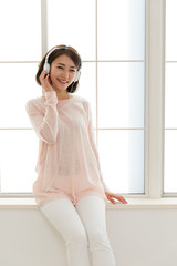 young asian woman listening music