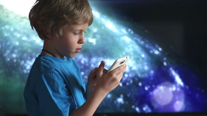boy and mobile device in hands using and playing