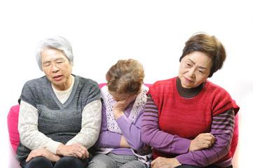 悩む高齢者3人の女性