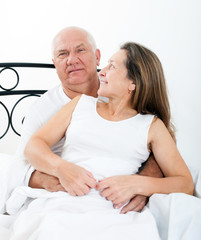 Mature man and woman on   bed