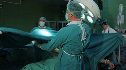 Surgeons performing surgical operation,isolated leg of patient